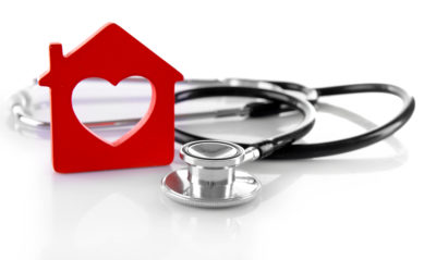 Red plastic house and stethoscope isolated on white background