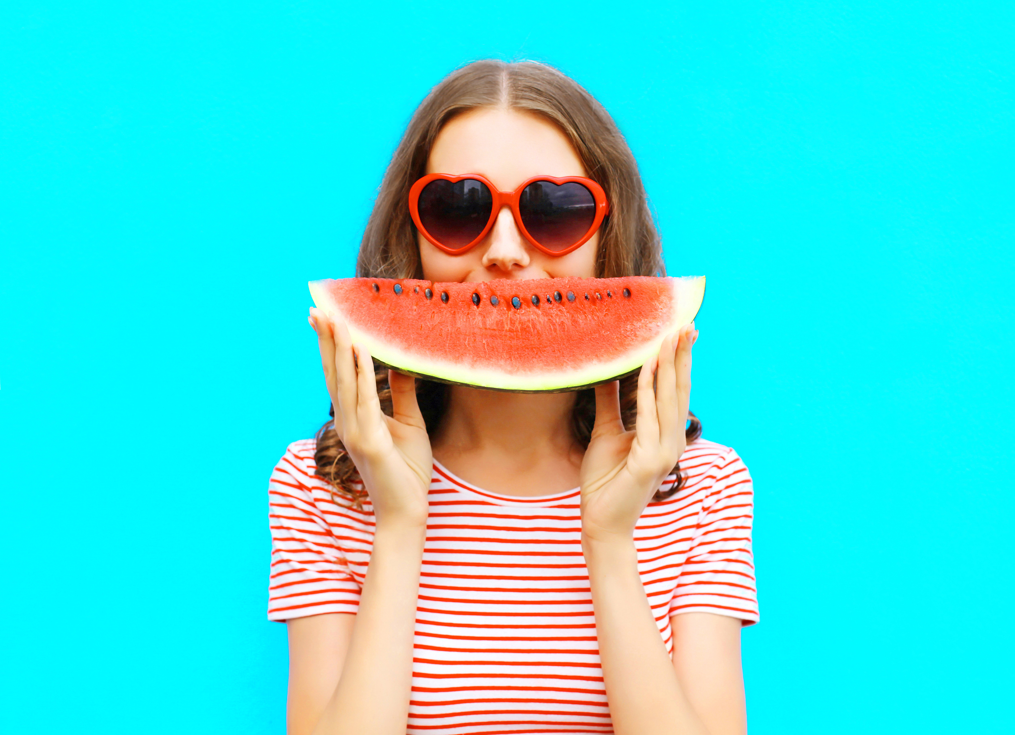 portrait happy young woman is holding slice of watermelon over colorful blue background