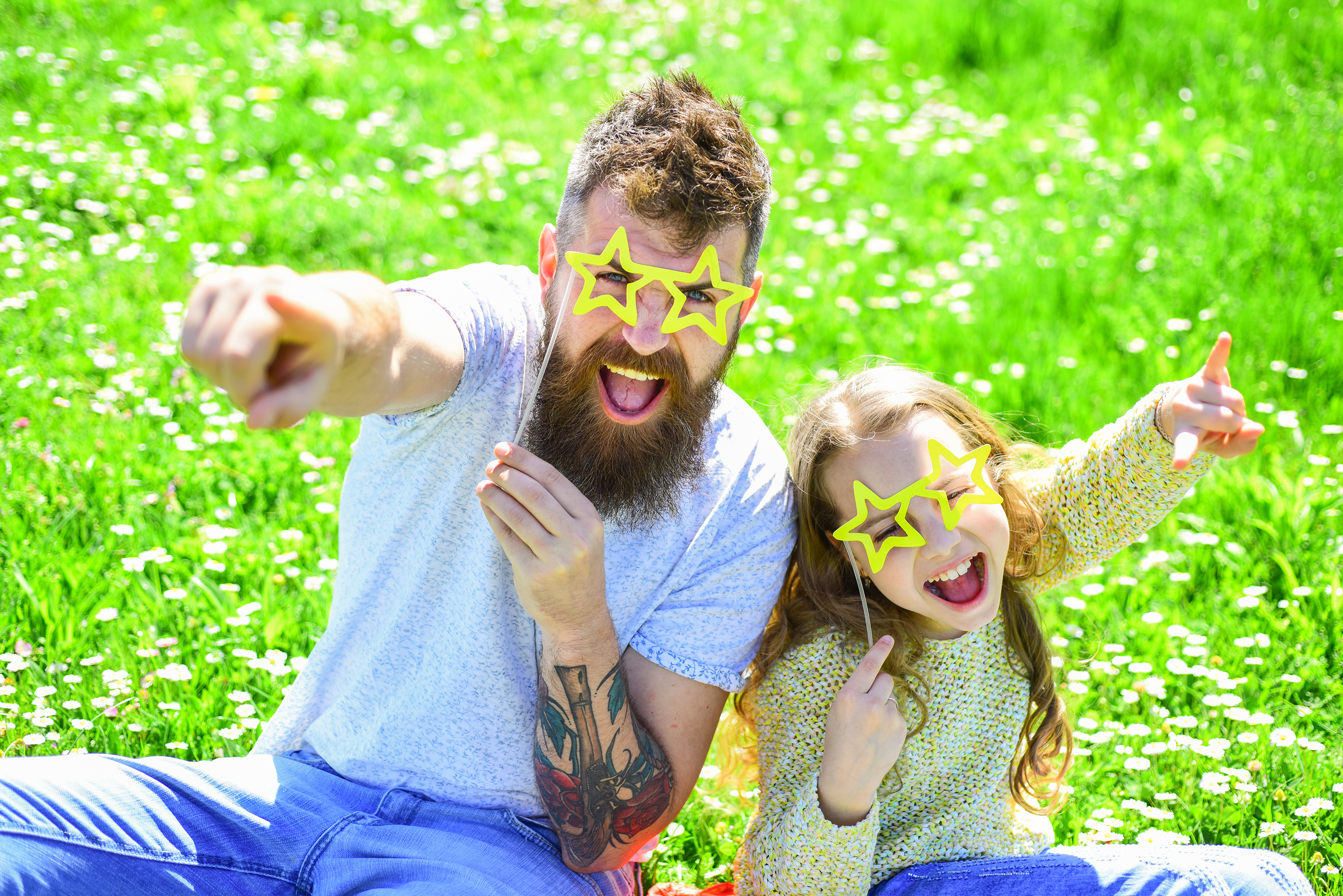 Child and dad posing with star shaped eyeglases photo booth attribute at meadow. Father and daughter sits on grass at free Reno concerts.